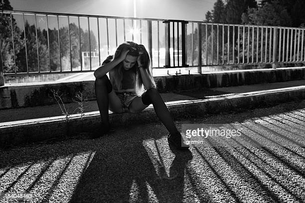 Young depressed woman sitting on the bridge
