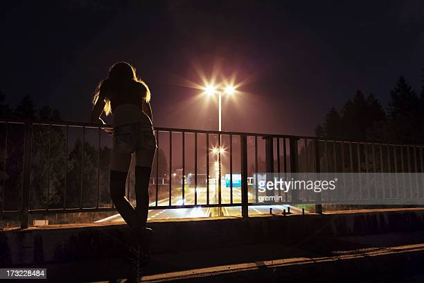 Young depressed woman standing on the bridge