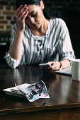 young depressed woman using smartphone  with crumpled photo of ex-boyfriend on foreground