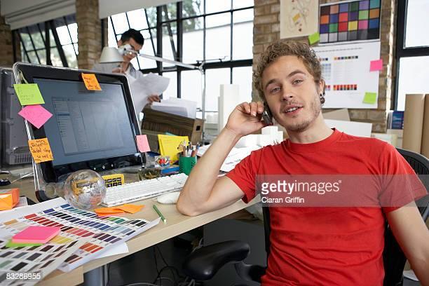 Junge designer spricht auf dem Mobiltelefon