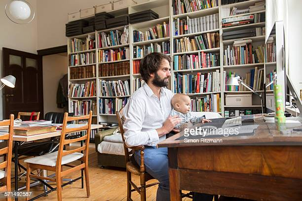 Young designer working in home with baby son