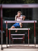 Young determined athlete jumping hurdles on a race.