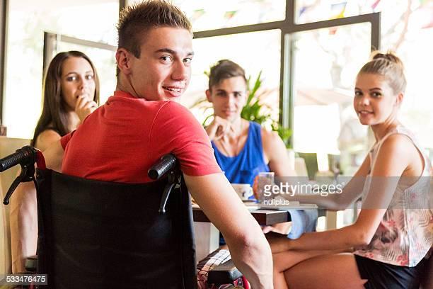 Minusválidos hombre joven divirtiéndose con sus amigos en el cafe