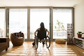 Beautiful young disabled woman in wheelchair at the window at home in her living room. Rear view.