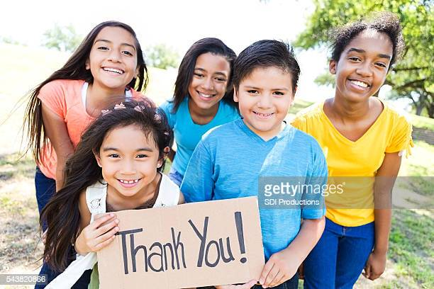 Young diverse friends in local park hold 'Thank You!' sign