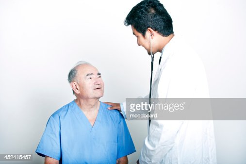 A young  Doctor comforting a Senior adult patient : Stock-Foto