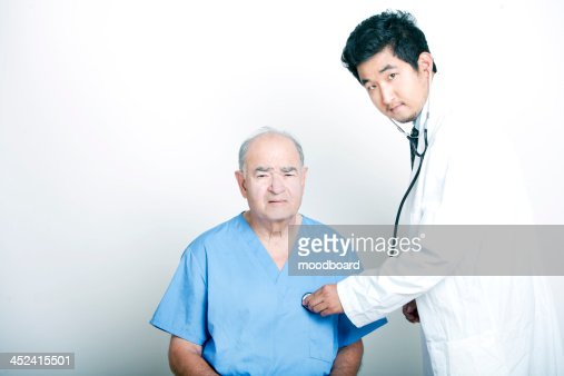 A young  Doctor comforting a Senior adult patient : Foto stock