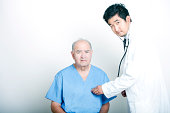A young  Doctor comforting a Senior adult patient
