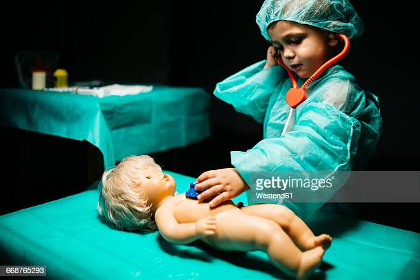 Young doctor healing a doll