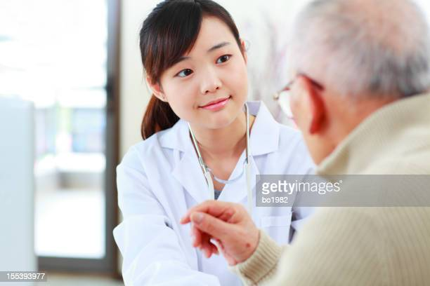 young doctor listening to senior patient