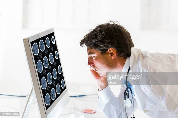 Young doctor watching CAT scan picture on monitor