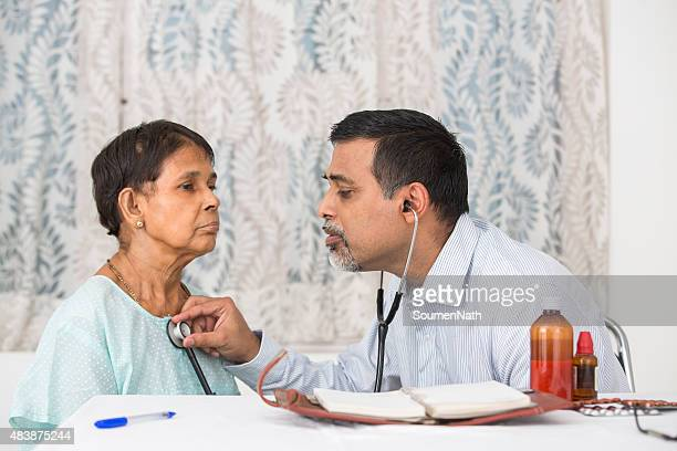 Young Doctor with an old woman doing a checkup
