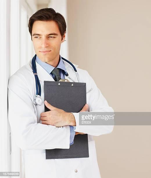 Junger Arzt mit Stethoskop und Notizblock in Gedanken versunken