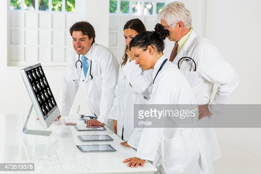 Young doctors  watching CAT scan picture on monitor