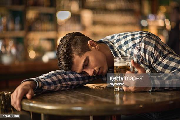 Young drunk man sleeping on the table in a bar.