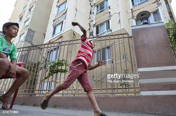 Young earthquake survivors play cricket outside the damaged apartment building after one month on May 25 2015 in Kathmandu Nepal Earthquake survivors...