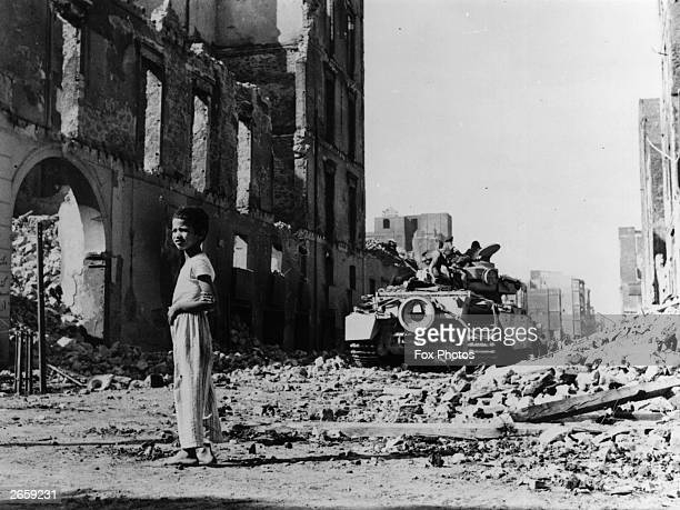 A young Egyptian boy stands amid the rubble of a wartorn street during the Suez Crisis A British tank can be seen in the background