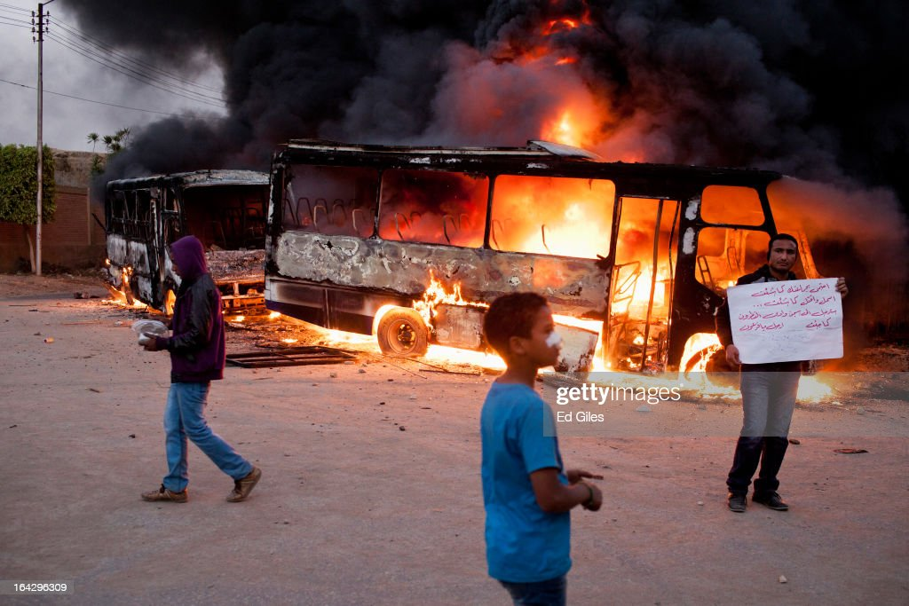 Young Egyptian men stand before a burning bus reportedly belonging to the Muslim Brotherhood during clashes between opposition demonstrators and supporters of the Muslim Brotherhood on March 22, 2013 in Cairo, Egypt. Opposition demonstrators converged on the headquarters of the Muslim Brotherhood in the Cairo suburb of Muqattam to protest against the government of President Mohammed Morsi, who is closely connected to the Muslim Brotherhood movement.