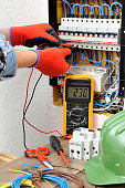 Young electrician technician measures with a multimeter the voltage in a electrical panel