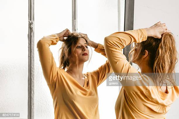 young elegant beautiful french woman dressing up hair in mirror