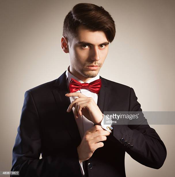 Young elegant businessman fixing his cufflink