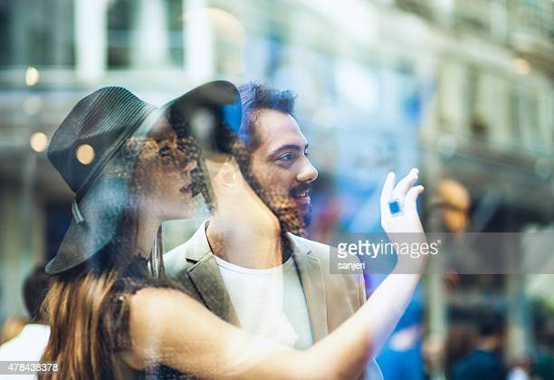 Young elegant couple on the street looking window display