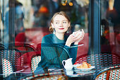 Young elegant woman drinking coffee in traditional cafe in Paris, France
