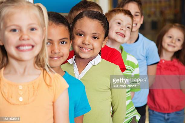 Young Elementary students smiling while waiting in line