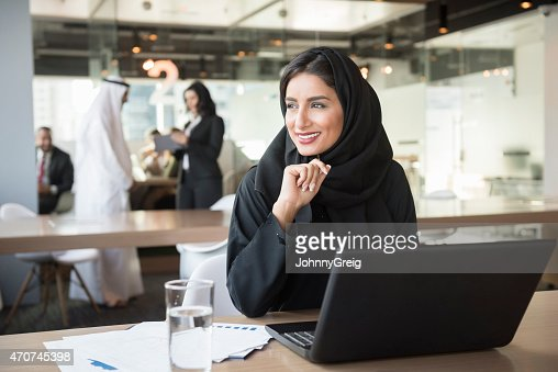 Young Emirati businesswoman looking away at conference table