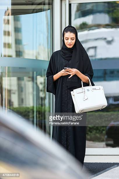 Young Emirati Woman in Black Abaya Checking Cellphone Outside Hotel