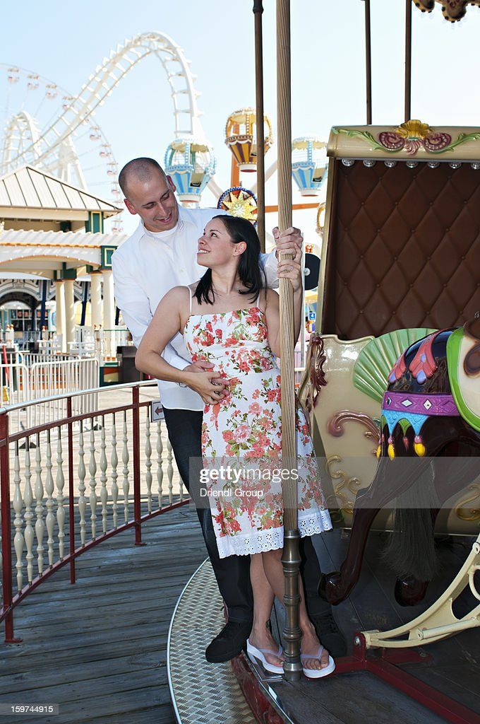 Young engaged couple on a carousel. : Stock Photo