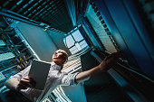 Young engineer businesswoman in network server room. Russia.