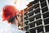 Young engineer in red helmet inspects construction of building. Bearded businessman on background of skyscraper under construction. Portrait of construction engineer on construction site background