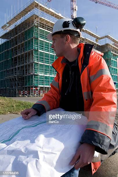 Jeune ingénieur sur un chantier de construction de grues d'échafaudages et de fond