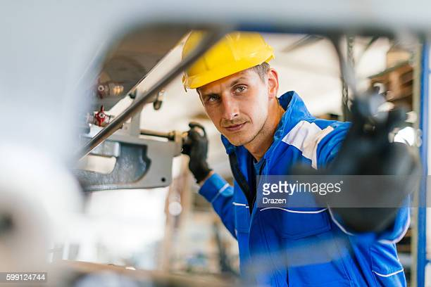 Young engineer testing the machine in factory