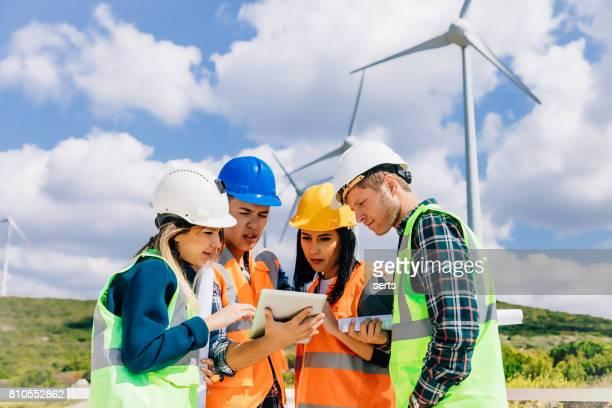 Junge Ingenieure und Arbeiter mit einem Treffen im Windpark