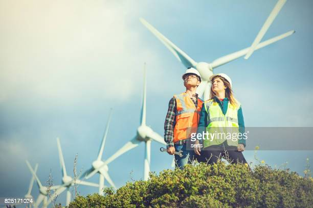 Young engineers looking and checking wind turbines at field