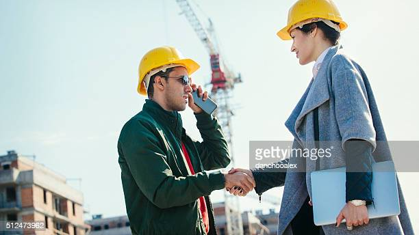 Young engineers shaking hands at construction site