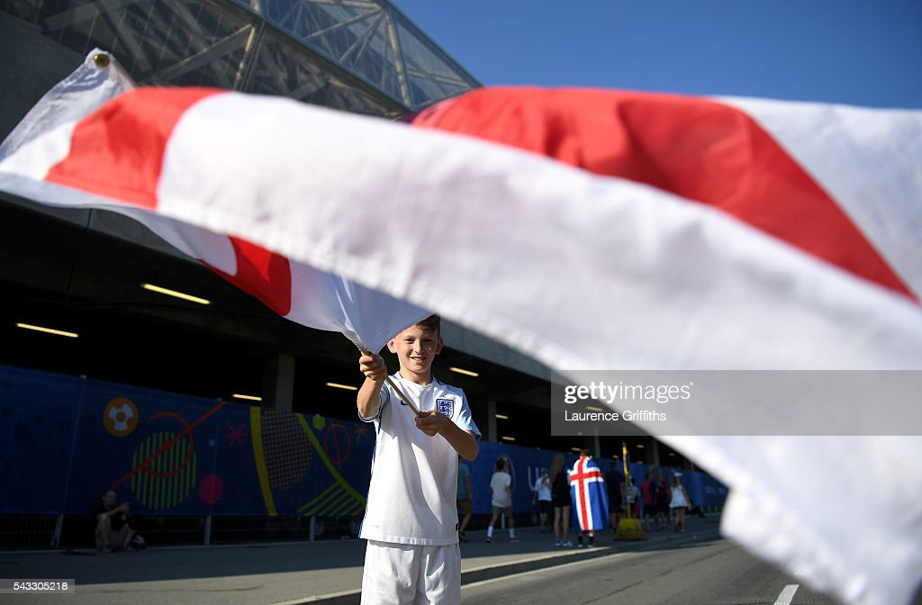 A young England fan waves an England flag as he poses for photographs outside the stadium prior to the UEFA EURO 2016 round of 16 match between England and Iceland at Allianz Riviera Stadium on June 27, 2016 in Nice, France.