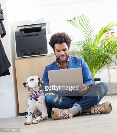 Young entrepreneur and his pet working : Stock Photo
