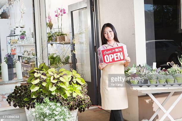 Jovem Empresário dono de loja de negócios segurando uma Placa de Open Hz