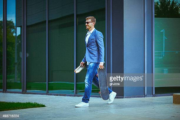 Young entrepreneur carrying skateboard on the way to work