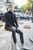 A successful young entrepreneur, having a break at lunch, relaxing while sitting in the city