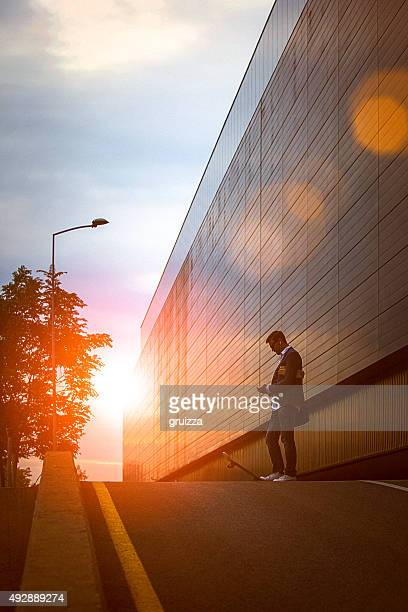 Young entrepreneur using smartphone in the urban environment at sunset