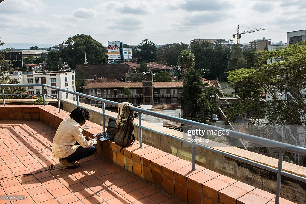 A young entrepreneur works outdoors on a laptop computer at the i-Hub technology innovation center in Nairobi, Kenya, on Thursday, July 23, 2015. Together, the entrepreneurs come up with concepts like Ushahidi, the open-source software that's used to share information and interactive maps to prevent conflicts and help aid agencies provide relief in disaster zones. Photographer: Waldo Swiegers/Bloomberg via Getty Images
