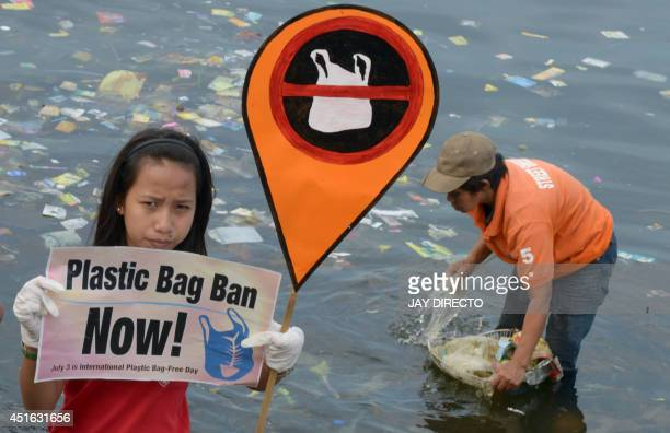 A young environmental activist holds a placard calling for a ban of the use of plastic bags in Manila on July 3 2014 while rubbish is removed from...