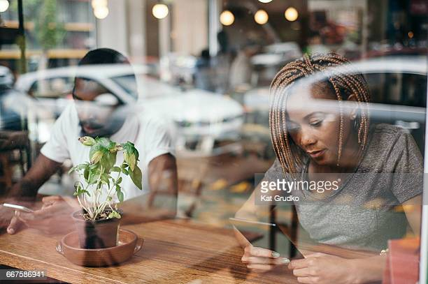 Young ethnic African couple sitting inside coffee shop on mobile devices taken through the window in trendy suburb in Braamfontein Johannesburg South Africa