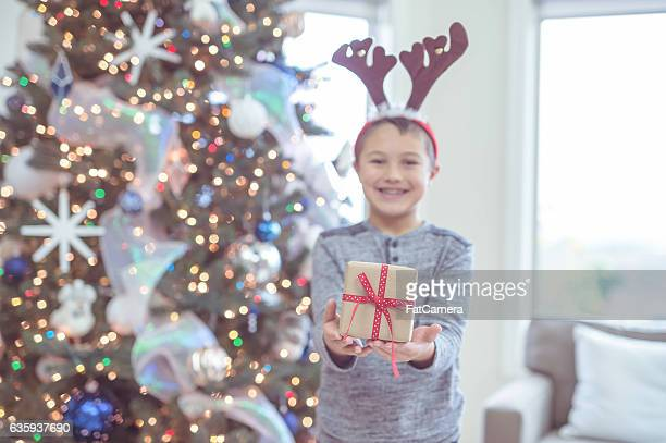 Young ethnic boy holding out a present by the christmas