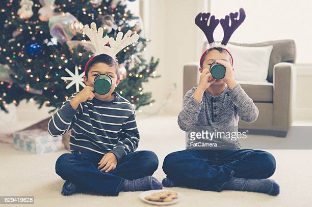Young ethnic boys drinking hot cocoa wearing antler hats