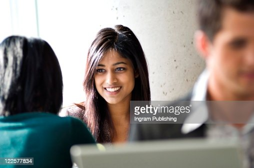 Young ethnic businesswoman chatting to colleague. : Stock Photo